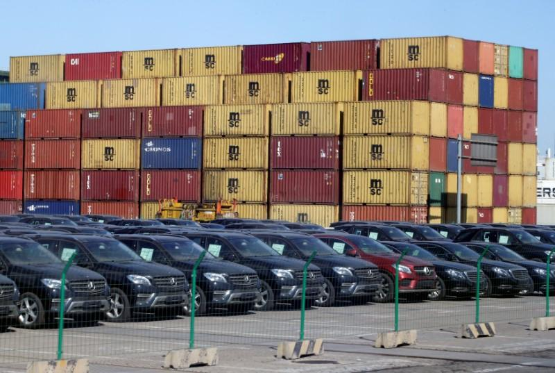 Imported Mercedes Benz cars are seen next to containers at Tianjin Port