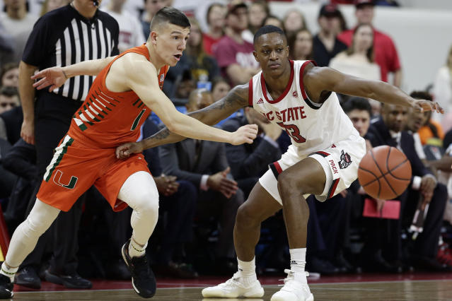 Miami guard Dejan Vasiljevic (1) and North Carolina State guard C.J. Bryce chase the ball during the second half of an NCAA college basketball game in Raleigh, N.C., Wednesday, Jan. 15, 2020. (AP Photo/Gerry Broome)