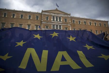 The word 'Yes' in Greek is seen on a banner during a pro-Euro rally in front of the parliament building, in Athens, Greece, June 30, 2015. REUTERS/Marko Djurica