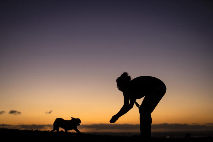 Rachel Ashton plays with her pug, Frankie, on the summit of Mount Roskill as the sunsets on a crisp winter evening in Auckland, New Zealand, on June 23, 2021. New Zealand has recorded its warmest June since recordkeeping began, as ski fields struggle to open and experts predict shorter southern winters in the future. (Jason Oxenham/New Zealand Herald via AP)