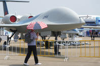 A man carrying an umbrella with the United States flag colors as he walks past the CH-6 drone during the 13th China International Aviation and Aerospace Exhibition, also known as Airshow China 2021 onTuesday, Sept. 28, 2021, in Zhuhai in southern China's Guangdong province. A state-owned Chinese aerospace company unveiled the military drone it says can stay aloft for up to 20 hours at altitudes as high as 15,000 meters (50,000 feet) at the opening Monday of the country's biggest air show.(AP Photo/Ng Han Guan)