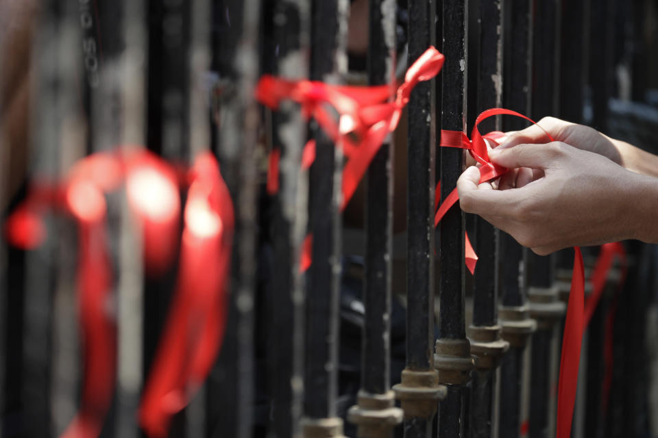 Demonstrators tie red ribbons to symbolize their protest against the early release of U.S. Marine Lance Cpl. Joseph Scott Pemberton during a rally outside the Department of Justice in Manila, Philippines, Thursday, Sept. 3, 2020. A Philippine court has ordered the early release for good conduct of Pemberton who was convicted in the 2014 killing of transgender Filipino Jennifer Laude which sparked anger in the former American colony. (AP Photo/Aaron Favila)