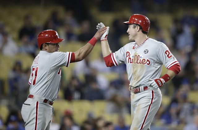 Philadelphia Phillies' Chase Utley, right, and Carlos Ruiz celebrate after they scored on a single hit by Marlon Byrd during the ninth inning of a baseball game against the Los Angeles Dodgers on Thursday, April 24, 2014, in Los Angeles. (AP Photo/Jae C. Hong)
