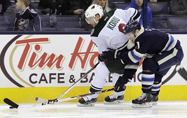 Minnesota Wild's Mikko Koivu, left, of Finland, and Columbus Blue Jackets' Matt Calvert chase a loose puck during the first period of an NHL hockey game on Friday, Dec. 6, 2013, in Columbus, Ohio. (AP Photo/Jay LaPrete)