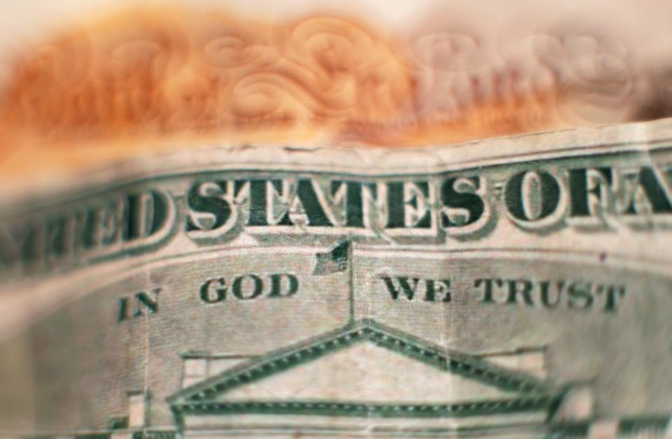 """The design on the reverse of a twenty dollar bill, featuring the official motto of the United States """"In God We Trust"""" above a depiction of the White House, placed in front of a ten pound note, in north London. PRESS ASSOCIATION Photo. Picture date: Friday January 27, 2017. Photo credit should read: Yui Mok/PA Wire"""
