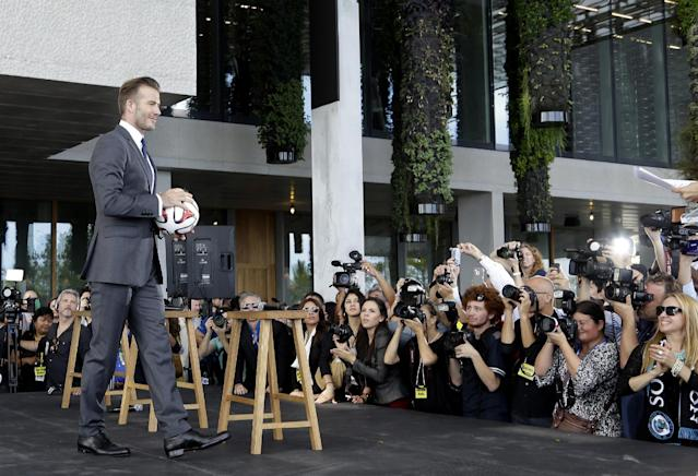 Former England soccer star David Beckham holds a soccer ball at a news conference where he announced he will exercise his option to purchase a Major League Soccer expansion team in Miami, Wednesday, Feb. 5, 2014, in Miami. (AP Photo/Lynne Sladky)