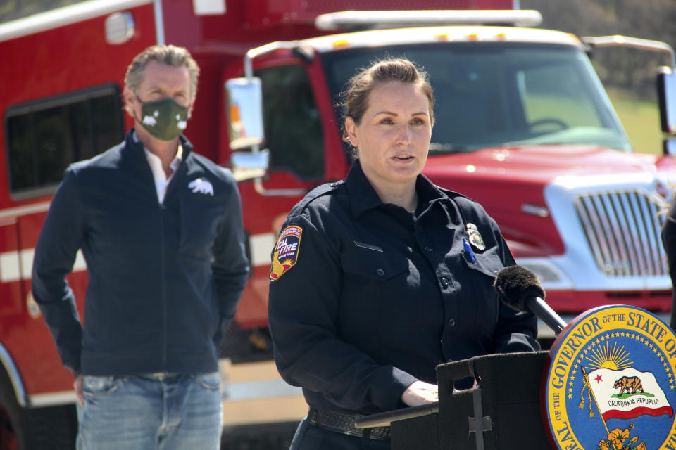 Beth Bowersox, a communications operator at the California Department of Forestry and Fire Protection, speaks to reporters during a news conference as California Gov. Gavin Newsom listens in the background on Tuesday, April 13, 2021, at the Loafer Creek State Recreation Area in Oroville, California. Newsom on Tuesday signed a law authorizing more than half a billion dollars in new spending to prepare for wildfire season. (AP Photo/Adam Beam)