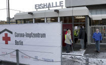 People wait at the entrance of a new open coronavirus, COVID-19, vaccination center in the 'Erika-Hess-Ice-Stadium' in Berlin, Germany, Thursday, Jan. 14, 2021. (AP Photo/Michael Sohn)