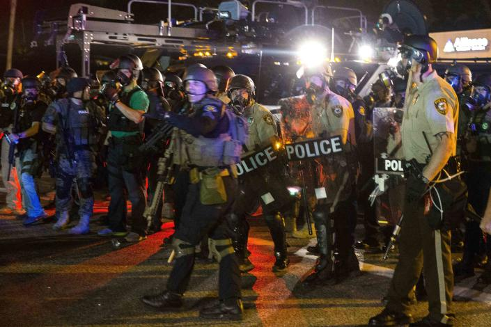 A line of police officers yells at a crowd of rowdy demonstrators during further protests in reaction to the shooting of Michael Brown near Ferguson, Missouri August 18, 2014. Police fired tear gas and stun grenades at protesters in Ferguson, Missouri on Monday, after days of unrest sparked by the fatal shooting of an unarmed black teenager by a white policeman. REUTERS/Lucas Jackson (UNITED STATES - Tags: CIVIL UNREST CRIME LAW SOCIETY)