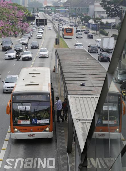 A man boards a bus at a bus stop in Sao Paulo, Brazil, Thursday, June 20, 2013. Leaders in Brazil's two biggest cities said Wednesday that they reversed an increase in bus and subway fares that ignited anti-government protests that have spread across the nation in the past week. (AP Photo/Nelson Antoine)