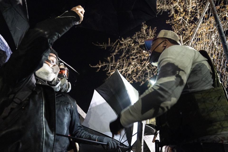 A Black man argues with demonstrators to stop preparing to use umbrellas to press against a perimeter security fence to agitate authorities during a protest decrying the shooting death of Daunte Wright outside the Brooklyn Center Police Department, Friday, April 16, 2021, in Brooklyn Center, Minn. (AP Photo/John Minchillo)