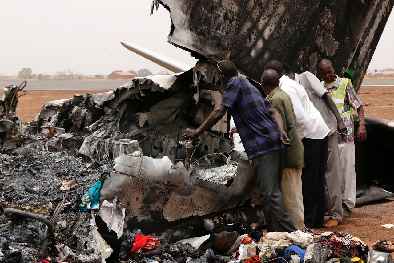 Aviation staff assess the wreckage of a South Supreme Airlines plane that crashed when it landed in the northwestern town of Wau from South Sudan's capital Juba, March 21, 2017. REUTERS/Jok Solomun FOR EDITORIAL USE ONLY. NO RESALES. NO ARCHIVE.      TPX IMAGES OF THE DAY