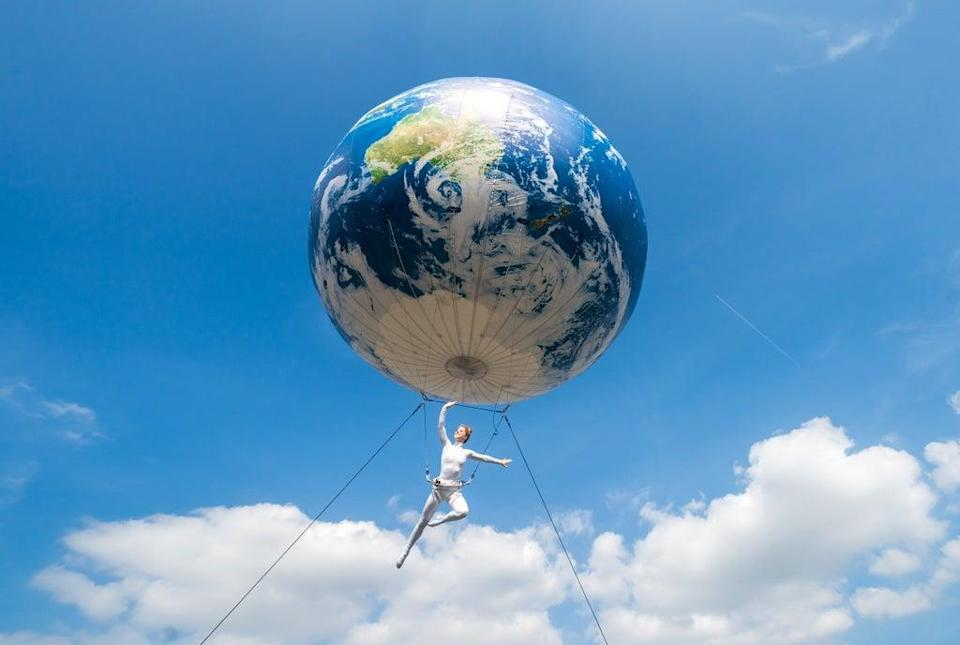An acrobat performs as she hangs under a heliosphere during the start of the Earth Spectacular celebration parade in Wakefield (PA)