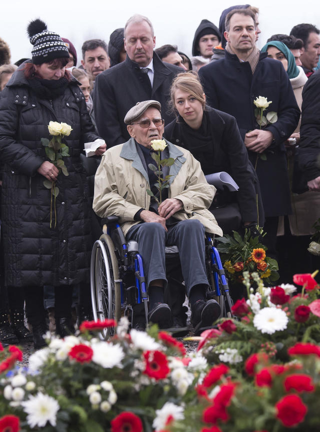 <p>Former Nazi concentration camp survivor Raymond Renaud of France, center, holds a white rose during the wreath-laying ceremony on occasion of the international Holocaust remembrance day (Jan. 27) in the former Nazi concentration camp Buchenwald near Weimar, Germany, Friday, Jan. 26, 2018. (Photo: Jens Meyer/AP) </p>