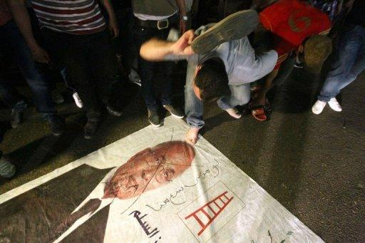 An Egyptian protester hits a portrait of presidential candidate and ex-prime minister Ahmed Shafiq in Cairo. His election headquarters were later torched