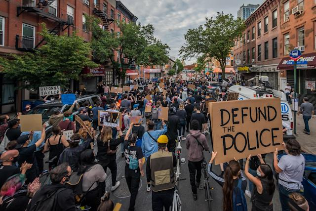 """Protesters in Brooklyn, N.Y., hold a """"Defund the Police"""" sign as thousands filled the streets and marched to demand justice for George Floyd, who was killed in May in police custody. (Erik McGregor/LightRocket via Getty Images)"""
