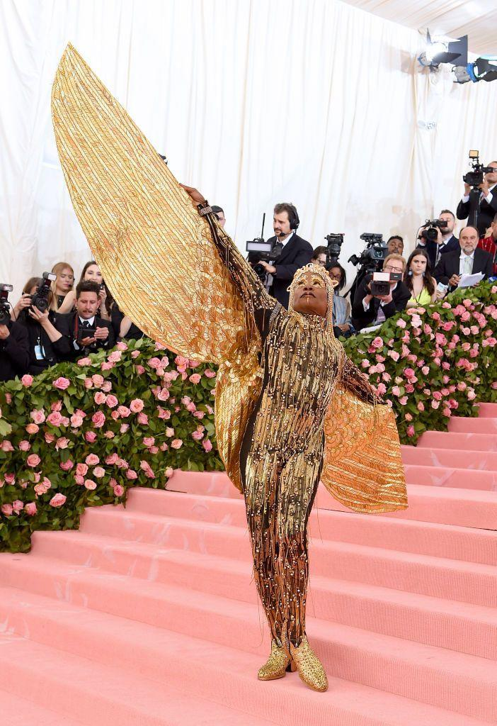 <p>Porter at the Met Gala, celebrating its theme, Camp: Notes on Fashion, in a gold fringe bodysuit, headpiece, and wings by The Blonds. </p>