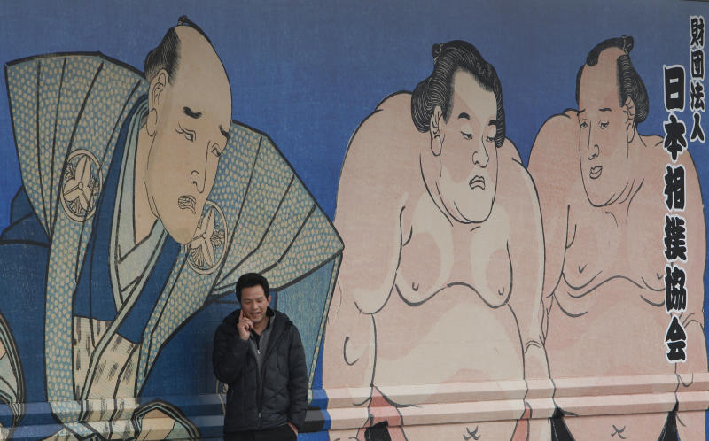 A media person talks on his cell phone outside Ryogoku Kokugikan sumo arena where the Japan Sumo Association is holding an emergency meeting in Tokyo Sunday, Feb. 6, 2011. In the meeting, the Japan Sumo Association decided to call off its Spring Grand Sumo Tournament scheduled for March, the first cancellation in 65 years, as the country's ancient sport grapples with a match-fixing scandal. (AP Photo/Shizuo Kambayashi)