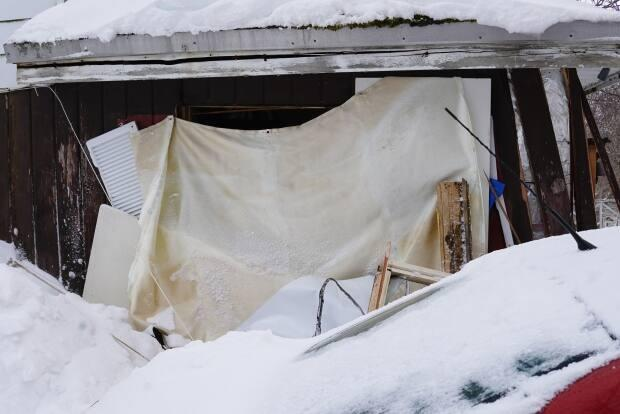 A tarp was thrown over a window smashed by a front-end loader at this home on Allandale Road on March 3. The tenants say their landlord smashed it out after pushing their car aside with the loader. (Ryan Cooke/CBC - image credit)