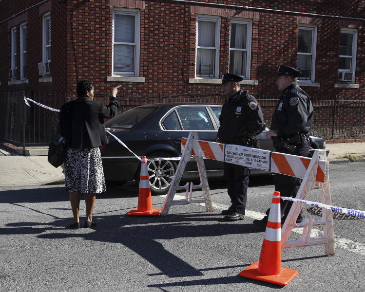 A pedestrian talks with police officers blocking the street where Vindalee Smith was murdered in New York, Sunday, Oct. 21, 2012. Smith, 38, who was eight months pregnant, was found stabbed to death Saturday in her apartment, the day before her wedding, police said. (AP Photo/Seth Wenig)