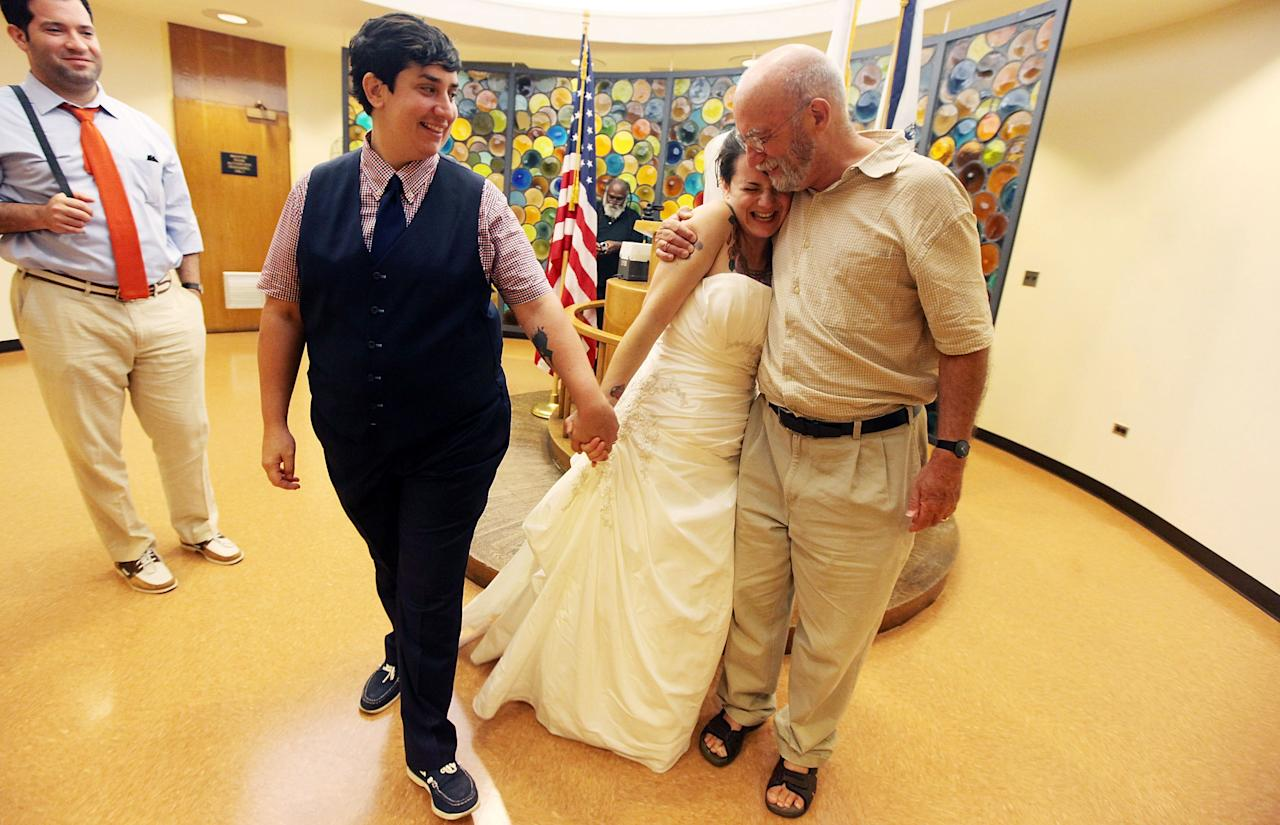 NEW YORK, NY - JULY 24:  Lailah Pepe (2nd R) hugs her father David Bragin after marrying Rachel Pepe (L) in a chapel at the Brooklyn City Clerk's office on July 24, 2011 in New York City. Today was the first day gay couples were allowed to legally marry in New York state after Gov. Andrew Cuomo signed the historic legislation into law.  (Photo by Mario Tama/Getty Images)