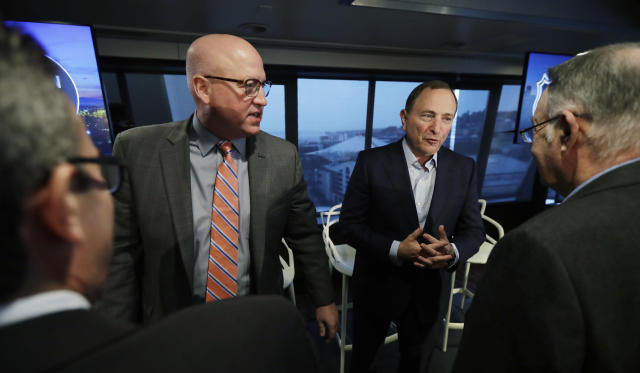 NHL Commissioner Gary Bettman, back right, and Deputy Commissioner Bill Daly, left, talk with reporters Wednesday, Jan. 9, 2019, following a news conference in Seattle. Bettman said the NHL has promised Seattle it will host the hockey All-Star Game within its first seven seasons. (AP Photo/Ted S. Warren)