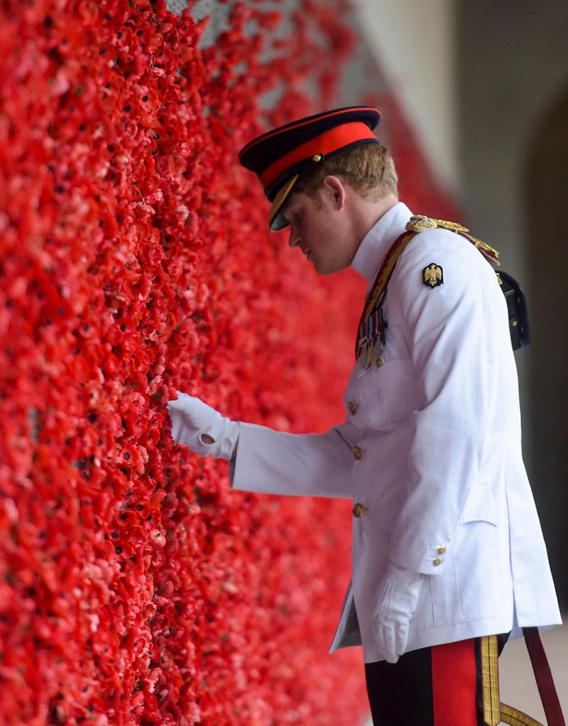 Prince Harry visits the Australian War Memorial in Canberra, Australia, Monday, April 6, 2015, laying a poppy on a bright red wall of poppies, wearing a white service uniform - Credit: Lukas Coch/AP