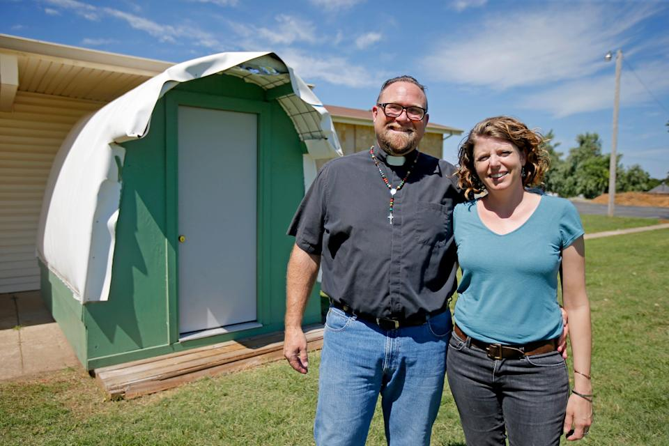 The Rev. Bo Ireland, leader of the Lazarus Community at Clark United Methodist Church, poses for a photo with his wife Alanna in front of a model of one of the structures that will be used for transitional housing for people experiencing homelessness.