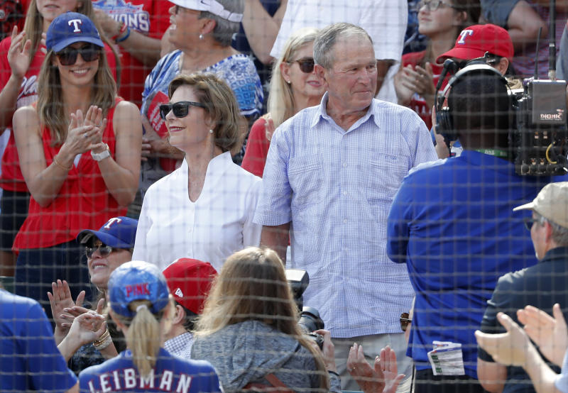 Former first lady Laura Bush, center left, and former President George W. Bush, center right, stand after being introduced in the fifth inning of a baseball game between the New York Yankees and Texas Rangers in Arlington, Texas, Sunday, Sept. 29, 2019. (AP Photo/Tony Gutierrez)