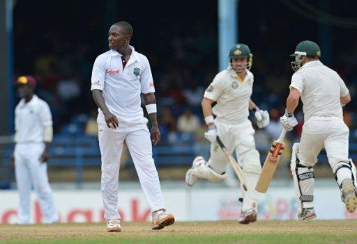 West Indies bowler Fidel Edwards (L) reacts to a shot as batsmen David Warner (R) and Ed Cowan (C) of Australia run the bases during the first day of the second-of-three Test matches between Australia and West Indies at Queen's Park Oval in Port of Spain, Trinidad
