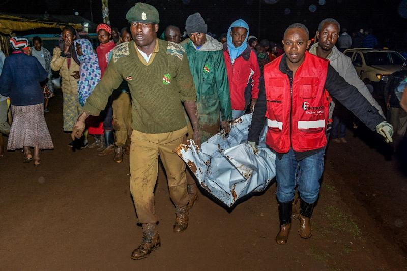 People carry a victim's body from a residential area on May 10, 2018 after the private Patel dam burst its bank at Solai, about 40 kilometres north of Nakuru, Kenya (AFP Photo/)