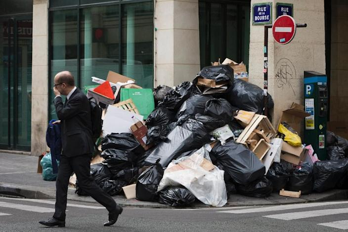 A man walks past a pile of un-collected rubbish on June 10, 2016 in Paris (AFP Photo/Joel Saget)