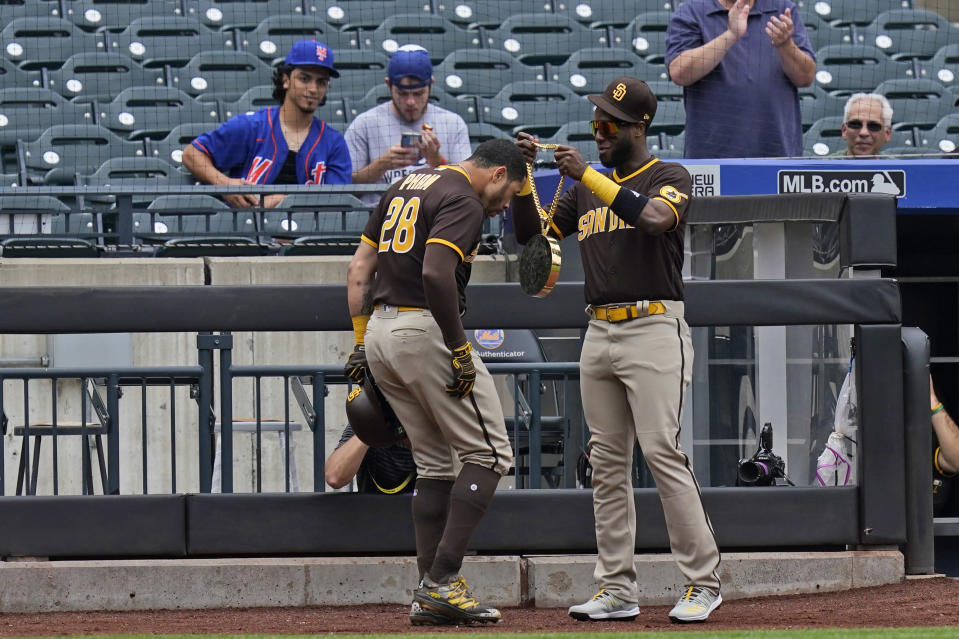 San Diego Padres' Jurickson Profar, right, puts a large necklace over Tommy Pham's head after Pham hit a solo home run during the first inning of a baseball game against the New York Mets at Citi Field, Sunday, June 13, 2021, in New York. (AP Photo/Seth Wenig)