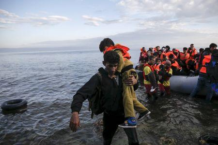 A migrant man carries a boy as refugees and migrants arrive on a raft on the Greek island of Lesbos, November 10, 2015.  REUTERS/Alkis Konstantinidis