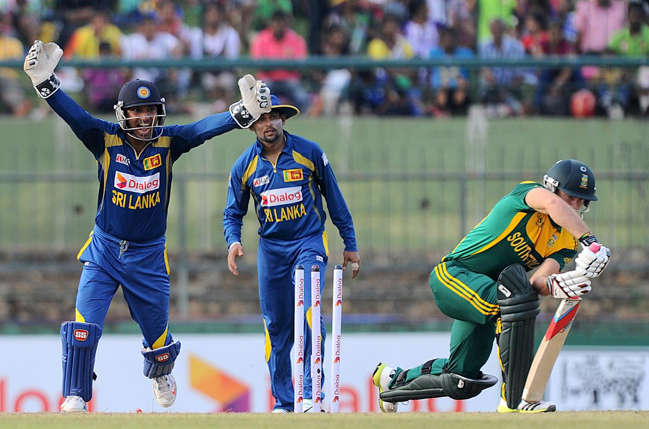 Sri Lankan wicketkeeper Kumar Sangakkara (L) celebrates the wicket of South African cricketer David Miller (R) during the fourth One Day International (ODI) cricket match between Sri Lanka and South Africa at the Pallekele International Cricket Stadium in Pallekele on July 28, 2013. AFP PHOTO/ Ishara S.KODIKARA