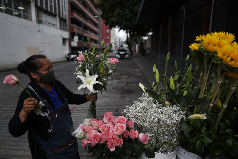 "Lucia Nieto assembles an arrangement of flowers for a customer, as she, her husband, and daughter sell fresh flowers from their family cart, in central Mexico City, Sunday, May 31, 2020. Mexico's capital plans to reopen certain sectors of the economy and public life beginning Monday, despite the city still being in the most serious ""red light"" phase of the coronavirus pandemic. (AP Photo/Rebecca Blackwell)"
