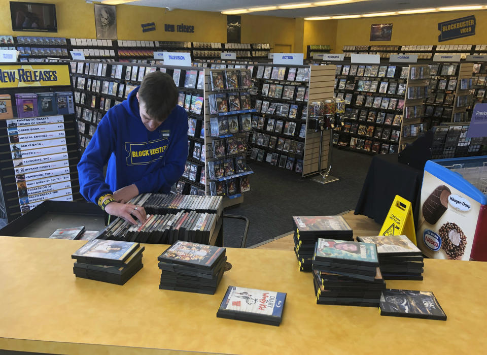 FILE - In this March 12, 2019, file photo employee Ryan Larrew alphabetizes returned movies before re-shelving them at the last Blockbuster store on the planet in Bend, Ore. The new Netflix movie called The Last Blockbuster that began airing March 15, 2021, is generating interest in the store, which became the last Blockbuster location on Earth when a location in Perth, Australia shut its doors in 2019. (AP Photo/Gillian Flaccus, File)