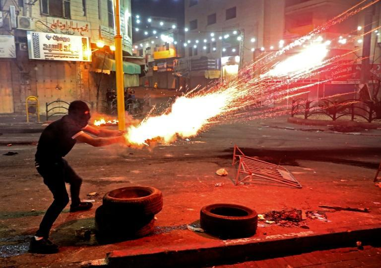 A Palestinian protester launches flares amid clashes with Israeli soldiers in Hebron in the occupied West Bank