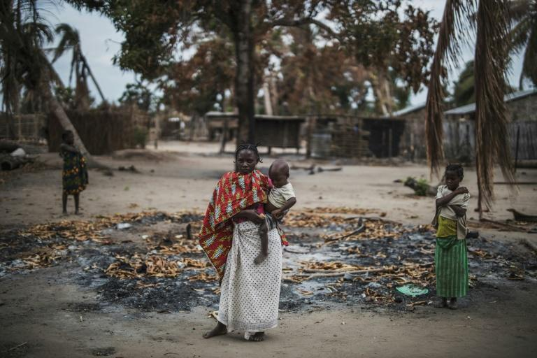 A woman and her child in the remains of a home in Aldeia da Paz, a village in Cabo Delgado province that was attacked in August 2019