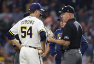 Umpire Jeff Nelson inspects the glove of Milwaukee Brewers pitcher Jake Cousins during the seventh inning of a baseball game against the St. Louis Cardinals, Thursday, Sept. 23, 2021, in Milwaukee. The glove was removed from the game. (AP Photo/Jeffrey Phelps)