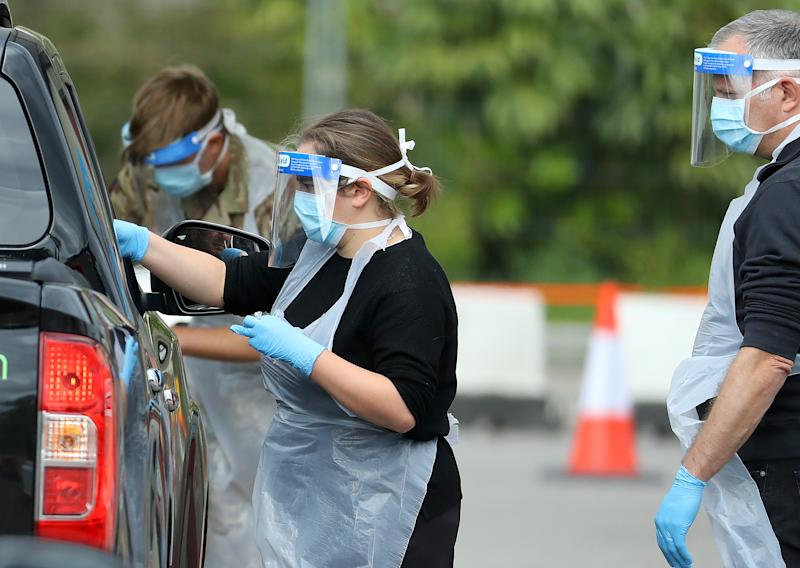 LONDON, UNITED KINGDOM - MAY 01: A Medical worker wearing a protective face mask and screen, disposable gloves and a plastic apron, takes a swap at a coronavirus drive-through testing center in the car park of the closed Chessington World of Adventures Resort theme park on May 01, 2020 in London, United Kingdom. British Prime Minister Boris Johnson, who returned to Downing Street this week after recovering from Covid-19, said the country needed to continue its lockdown measures to avoid a second spike in infections. (Photo by Warren Little/Getty Images)