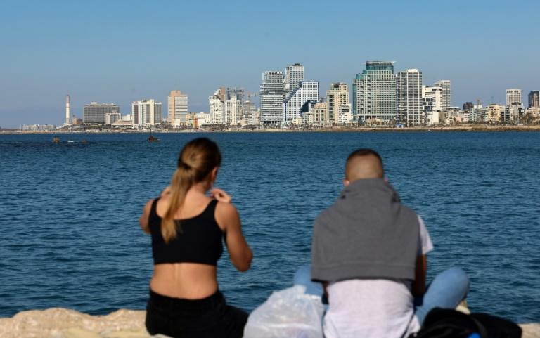 A young couple share a picnic in front of the skyline of Tel Aviv -- a city where rents are among the highest in the world