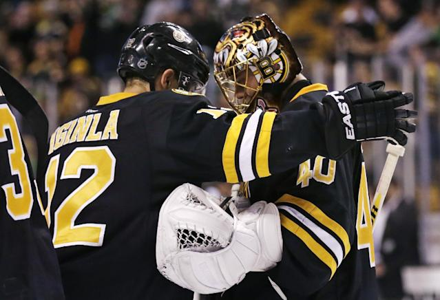 Boston Bruins goalie Tuukka Rask (40) is congratulated by Boston Bruins right wing Jarome Iginla after defeating the Minnesota Wild 4-1 in an NHL hockey game, Monday, March 17, 2014, in Boston. Iginla had two goals and Rask made 33 saves in the Bruins win. (AP Photo/Charles Krupa)