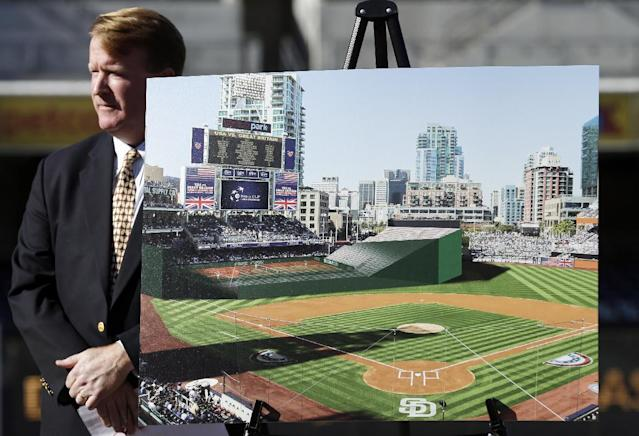 Jeff Ryan, the U.S. Tennis Association's team events director, stands behind an image of the proposed Davis Cup tennis venue, to be built in the outfield of the San Diego Padres' PETCO Park baseball stadium, during an announcement Tuesday, Nov. 5, 2013, in San Diego. Ryan announced plans to play the first-round Davis Cup match between Britain and the United States in January of 2014 in San Diego. (AP Photo/Gregory Bull)