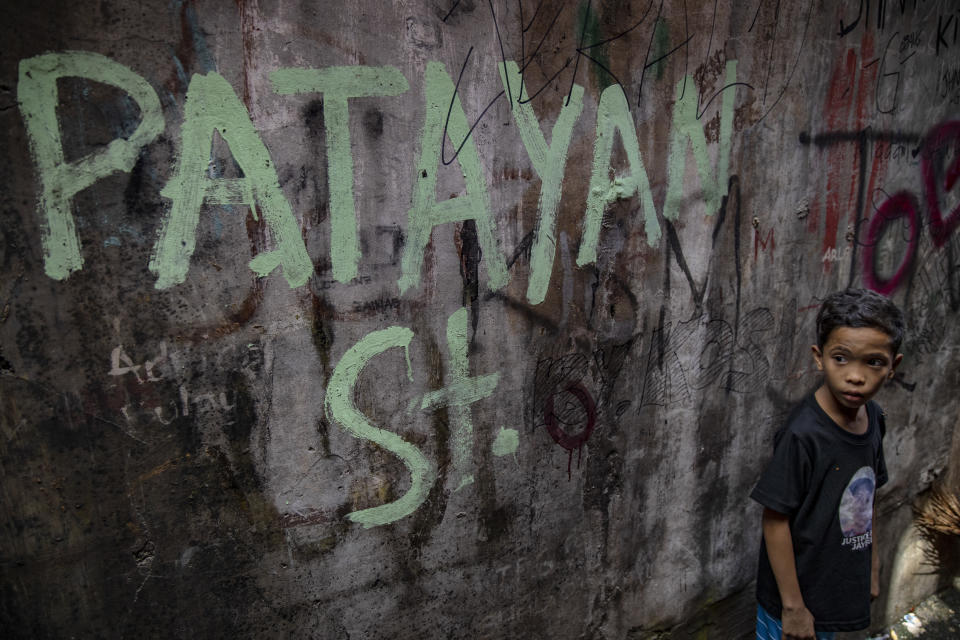 FILE PHOTO: A child walks past a graffiti on a wall with the words