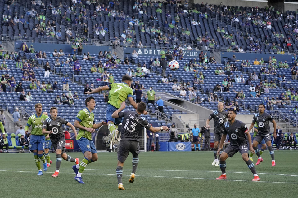 Seattle Sounders midfielder Cristian Roldan (7) heads the ball in front of Minnesota United midfielder Ethan Finlay (13) during the first half of an MLS soccer match Friday, April 16, 2021, in Seattle. (AP Photo/Ted S. Warren)