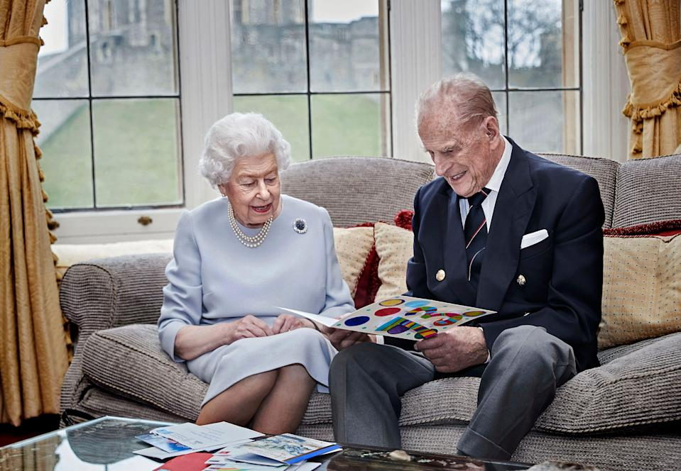 Queen Elizabeth II and Prince Philip, Duke of Edinburgh, look at homemade wedding anniversary cards given to them by their great-grandchildren at Windsor Castle ahead of their 73rd anniversary, Nov. 17, 2020.