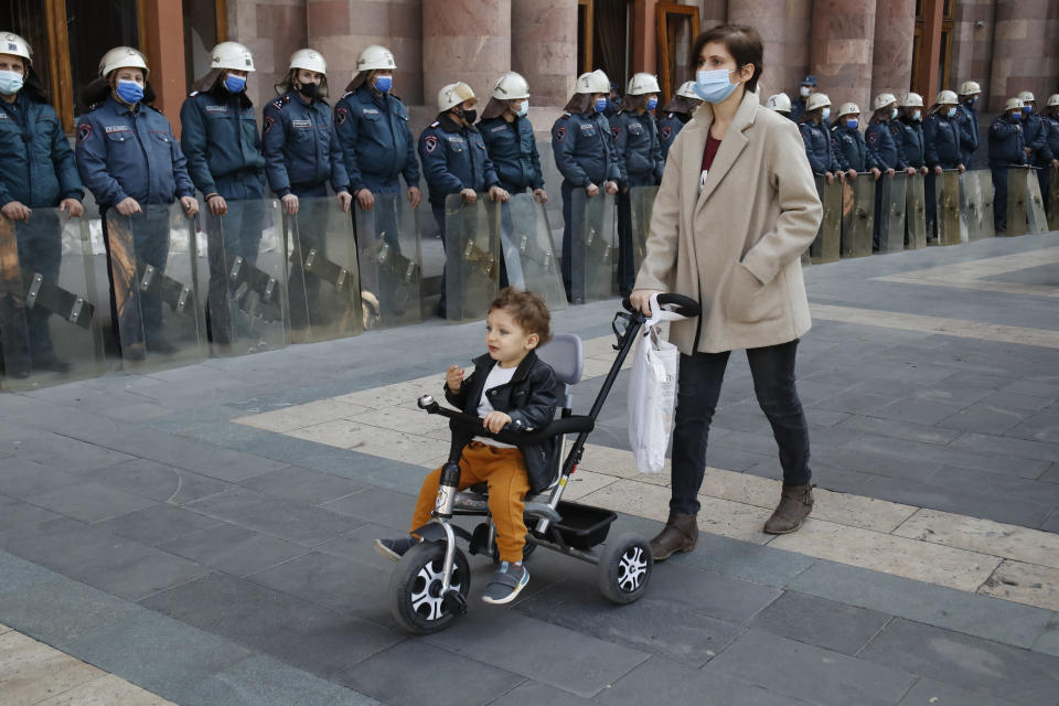 """A woman wheels a stroller with a child as police officers guard in front of the government building in Yerevan, Armenia, Tuesday, Nov. 10, 2020. Some thousands of people streamed to the main square in the Armenian capital early Tuesday to protest the agreement to halt fighting over the Nagorno-Karabakh region, many shouting """"We won't give up our land."""" Some of them broke into the main government building, saying they were searching for Pashinian, who apparently had already departed. (AP Photo/Dmitri Lovetsky)"""
