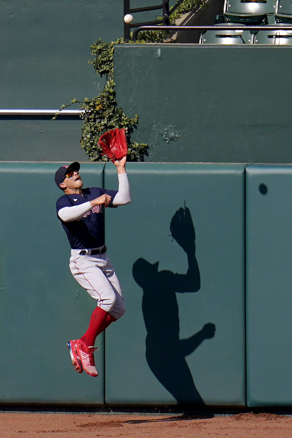 Boston Red Sox center fielder Enrique Hernandez goes up to make a catch near the wall on a ball hit by Baltimore Orioles' Rio Ruiz during the eighth inning of a baseball game, Sunday, April 11, 2021, in Baltimore. (AP Photo/Julio Cortez)