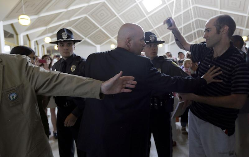 Capitol police push back spectators as a woman is arrested as people gather outside the Senate chamber at the state legislature while Senate Republicans gave their final approval to legislation requiring additional rules surrounding abortions in North Carolina, even as hundreds of protesters against the bill watched from the gallery in Raleigh, N.C., Wednesday, July 3, 2013. The Senate voted 29-12 Wednesday for the measure that would direct regulators to change abortion clinic rules so they're similar to those for ambulatory surgery centers. The bill would still need House approval, which couldn't happen until at least next week. (AP Photo/Gerry Broome)